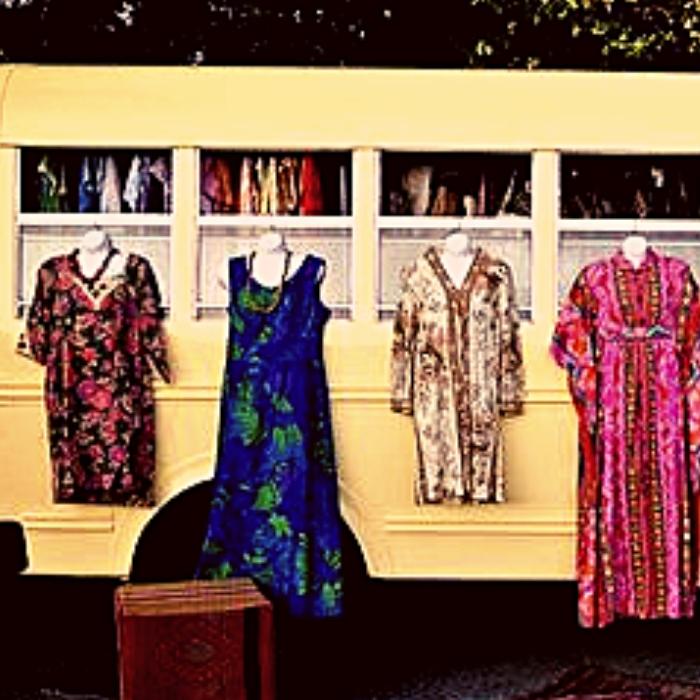 vintage dresses hung outside windows of a mobile fashion bus