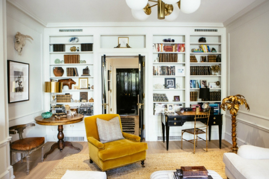 a velvet yellow mustard chair center of room filled with antiques
