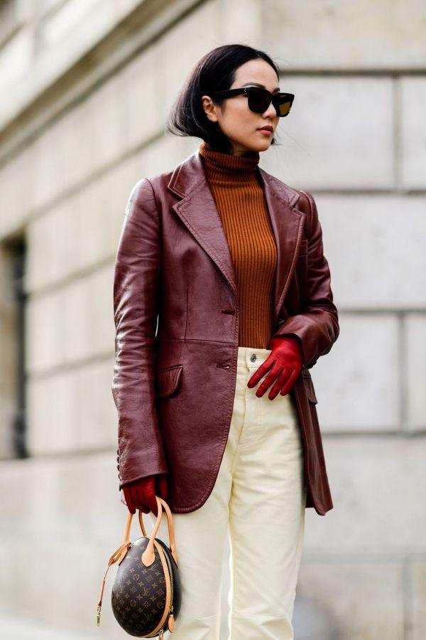 woman on street wearing burgundy blazer and brown sweater