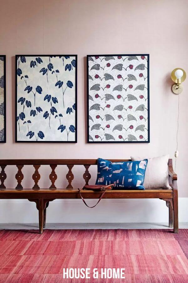 long brown bench with blue pillow and large artwork in entry way.