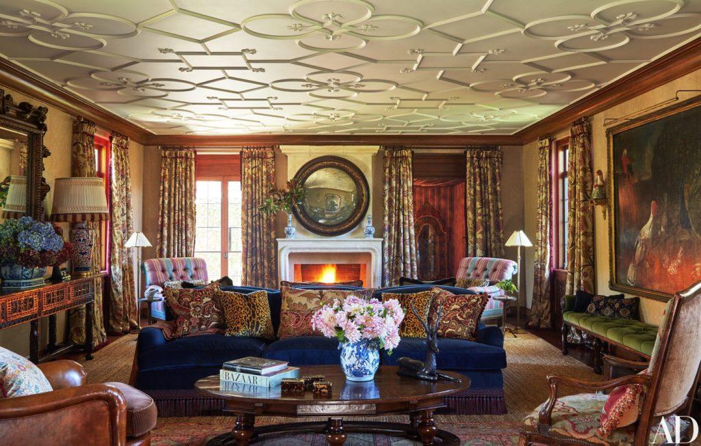 upholstered blue silk velvet sofa with vintage tapestry pillows in Tommy Hilfiger living room