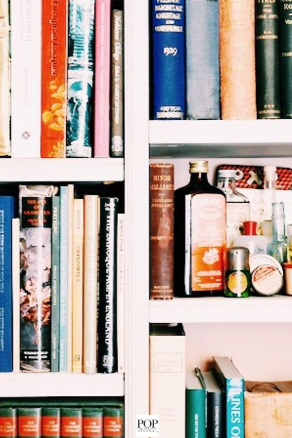 organized bookshelves with vintage bottles