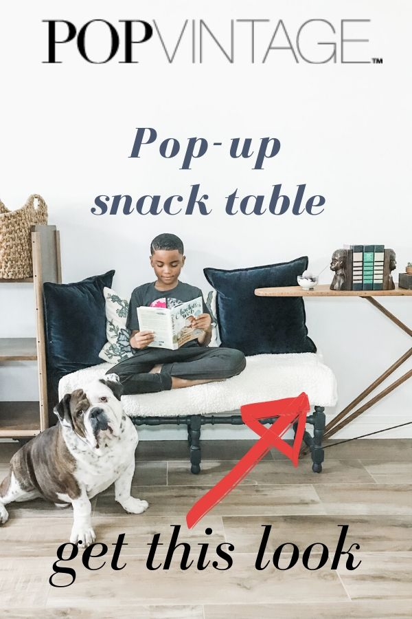 boy reading book and using an old wooden ironing board as a snack table