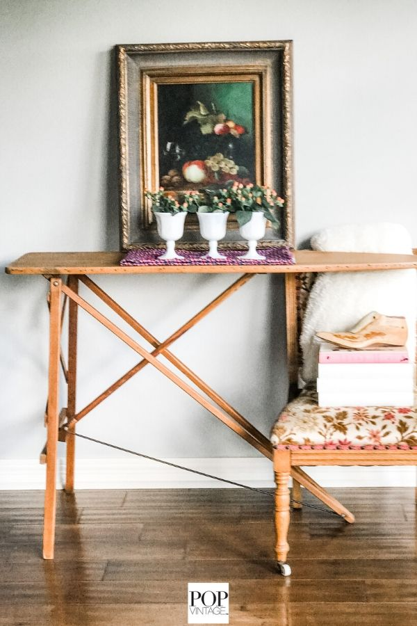 a vintage wood ironing board is repurposed as a flower stand